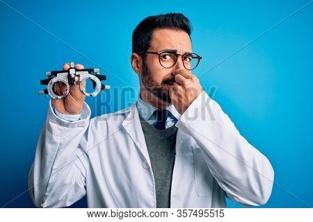 Young handsome optical man with beard holding optometry glasses over blue background smelling something stinky and disgusting, intolerable smell, holding breath with fingers on nose. Bad smell