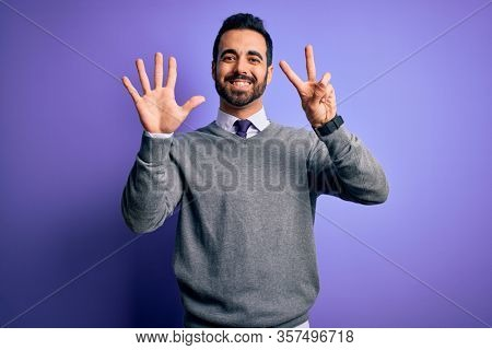 Handsome businessman with beard wearing casual tie standing over purple background showing and pointing up with fingers number seven while smiling confident and happy.