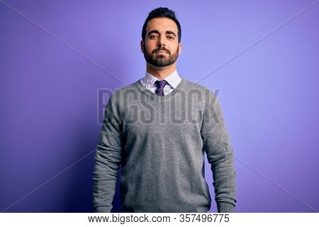 Handsome businessman with beard wearing casual tie standing over purple background Relaxed with serious expression on face. Simple and natural looking at the camera.