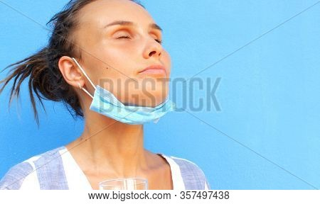 Woman in medical mask on a blue background. Concept for COVID-19, medical articles and news