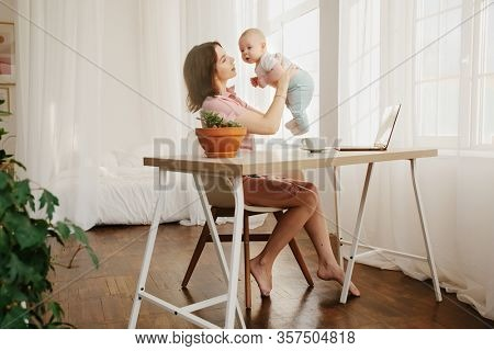 Mom plays with her baby. Home office, freelance.