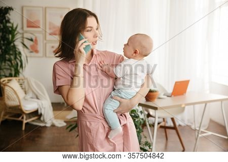 A young mother holds a baby in her arms and talks on the phone.