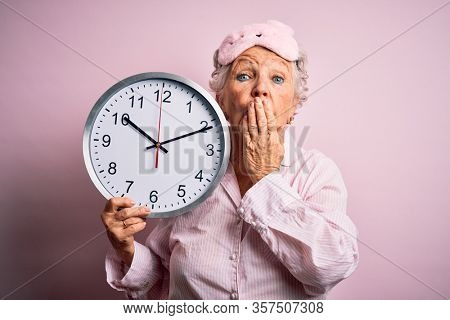 Senior beautiful woman wearing sleep mask holding big clock over isolated pink background cover mouth with hand shocked with shame for mistake, expression of fear, scared in silence, secret concept