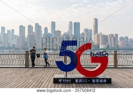 Chongqing, China - Sep 1, 2019: People Using Smartphone Near A 5g Sign. 5g Is The Next Generation Of