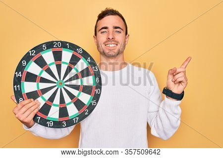 Young handsome man with blue eyes holding dartboard over isolated yellow background very happy pointing with hand and finger to the side