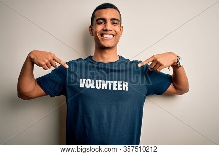 Young handsome african american man volunteering wearing t-shirt with volunteer message looking confident with smile on face, pointing oneself with fingers proud and happy.