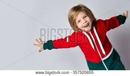 Portrait Of Cheerful Active Frolic Blond Kid Boy In Dark Gray And Red Hoodie Playing Aircraft Runnin