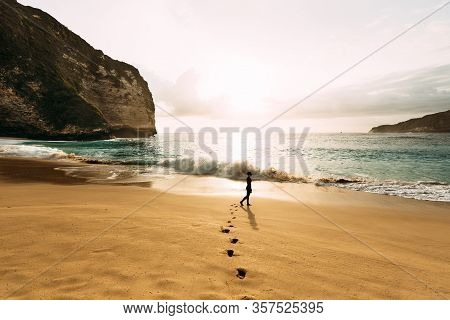 A Lonely Man Stands On The Beach. A Man Meets The Sunset On The Beach In Indonesia. Steps On The San