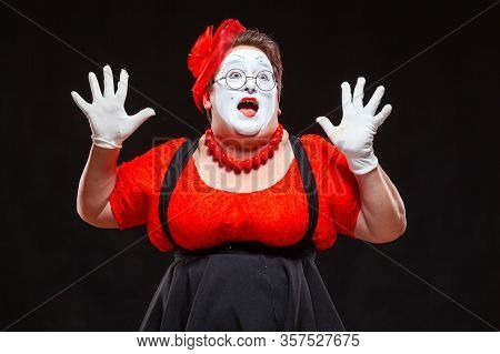 Portrait Of Female Mime Artist, Isolated On Black Background. Racy Woman Throwing Up Her Hands And S