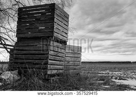 Three Wooden Crates Standing By The Fields Waiting For Spring At The Northern Finland.