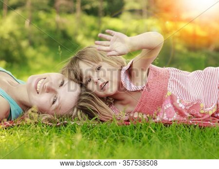 Mother With Her Happy Little Daughter Lie On The Grass