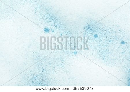 Foamy Texture With Bubbles On Blue Background. Moisturizing Or Cleansing Cosmetics Foam Backdrop. Co