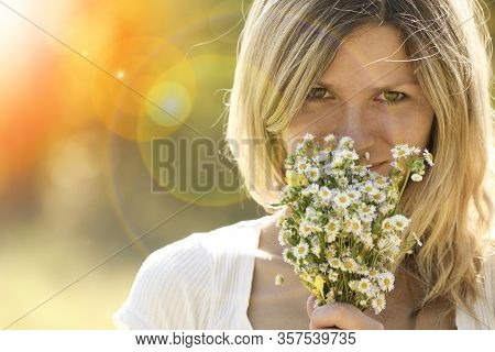 Young Girl With A Bouquet Of Flowers On The Nature