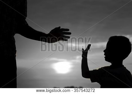 Silhouette The Parent Holds The Hand Of A Small Child