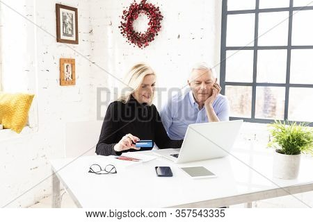 Happy Senior Couple Using Bank Card And Notebook While Shopping Online