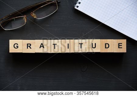 Modern Business Buzzword - Gratitude. Top View On Glasses And Notepad With Wooden Blocks. Close Up.