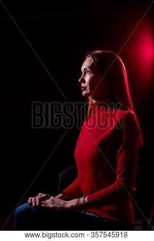 Portrait Of Elegant Woman With Long Hair In Red Sweater And Dark Background With Red Light. Model Po