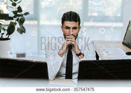 Pensive Bi-racial Trader Looking At Computers In Office