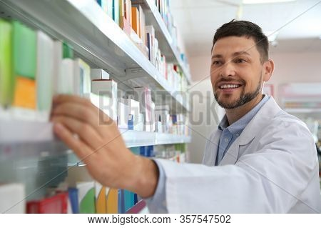 Professional Pharmacist Near Shelves With Medicines In Drugstore