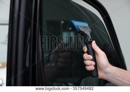 Worker Washing Tinted Car Window In Workshop, Closeup