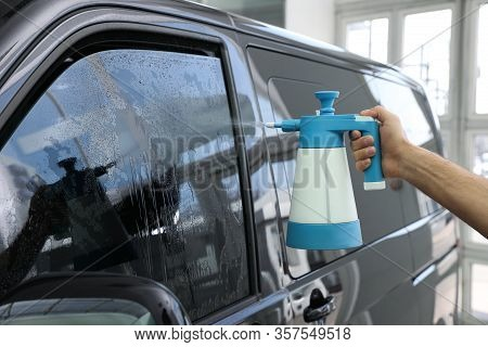 Worker Spraying Water Onto Tinted Car Window  In Workshop, Closeup