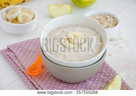 Baby Food. Creamy Oatmeal With Banana Slices And Apple In A Bowl With A Spoon On A Light Background.