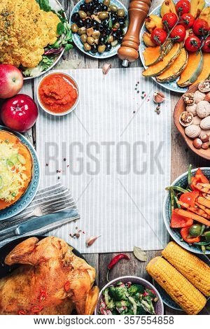 Whole Roasted Chicken, Rice, Pumpkin, Corn, Honey, Nuts, Vegetable Salads Over Wooden Background. To