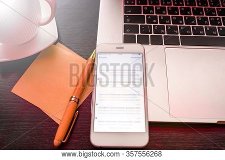 Modern White Mobile Phone With Blurred Text Message On Screen Lying On Open Laptop Computer Near Cle