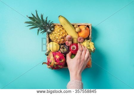 Tropical Fruits On Blue Background. Rattan Box Full Of Exotic Thailand Fruits - Pineapple, Pitahaya,