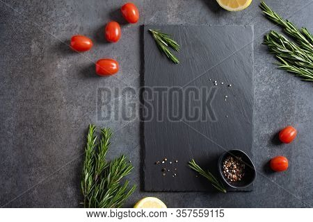 Empty Black Stone Board And Ingredients On Dark Background. Free Space For Text And Brand Product. C