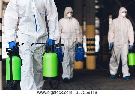 Warning, Coronavirus Disinfection. Men In Virus Protective Suits Carrying Spray Bottles With Chemica