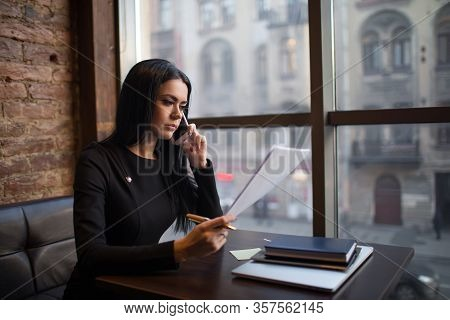 Serious Successful Business Woman Reading Summary And Talking With Workers Via Mobile Phone, Sitting