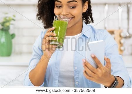 Morning Smoothie. Closeup Portrait Of African Woman Using Phone And Drinking Homemade Detox Juice In