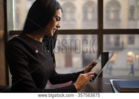 Happy Smiling Woman Entrepreneur Using Portable Touch Pad Computer While Sitting In Office Interior