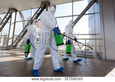 Protection Of Coronavirus Biohazard. Men In Respirators And Protective Suits Cleaning Public Places