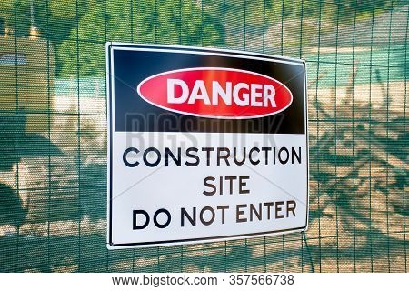 Danger Construction Site Do Not Enter Sign On A Fence Surrounding The Demolished Buiding