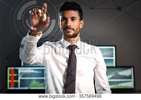 Selective Focus Of Handsome Bi-racial Trader Pointing With Finger Near Computers On Background
