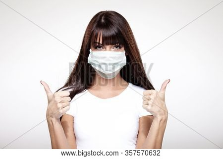 corona virus concept. happy young healthy woman in protective mask showing thumbs up isolated on white background