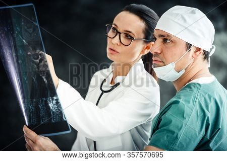 healthcare in hospital concept. male surgeon and female doctor or nurse reviewing x-ray scan results