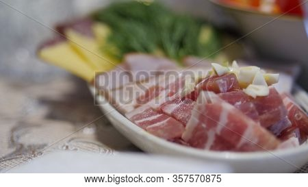 Table Setting, Pork Belly, Cheese, Smoked Sausage And Ham Cut Into Slices On An Oblong Plate. Dill D