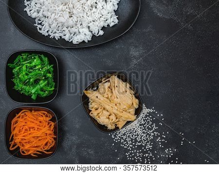 Rice With Korean Carrots, Soy Asparagus, Chuka And Scattered Sesame Seeds On Black Background Top Vi