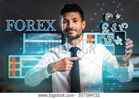 Smiling Bi-racial Trader Pointing With Finger At Smartphone Near Forex Letters And Money Signs