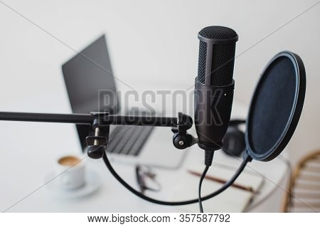 Items For Recording Podcast: Professional Microphone, Earphones And Laptop On White Table In Cozy Ho