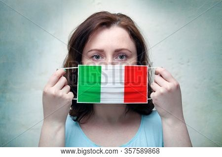Studio portrait of a woman in a mask on a gray background. ?oronavirus epidemic in Italy..