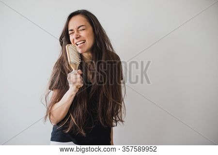 Young Beautiful Happy Woman Brushes Her Long Healthy Hair With Wooden Hairbrush On White Background.
