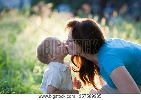 Happy mother with  children in garden. Happy young boy kisses mother.