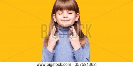 Funny Little Girl Crossing Fingers, Hoping Her Wish Come True, Isolated On Yellow. Portrait Of Small