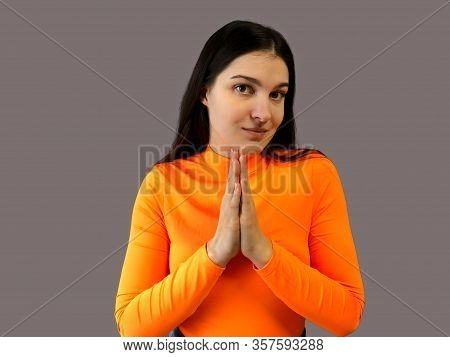 Young Beautiful Girl With Dark Hair In A Bright Orange Sweater On A Gray Background. Implore