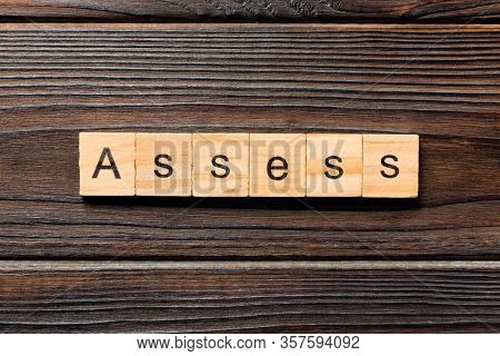 Assess Word Written On Wood Block. Assess Text On Wooden Table For Your Desing, Concept