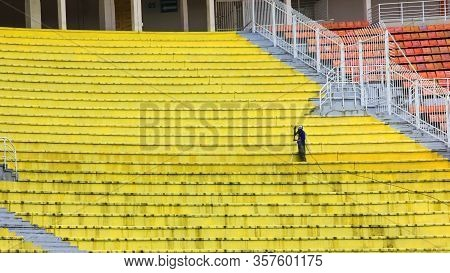 Cleaning Service Worker Is Washing By Hose Yellow Dirty Plastic Seats On Empty Grandstand Of Famous